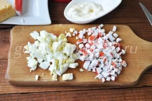 Нарежьте крабовые и яйца